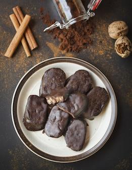 Hausgemachte schokoriegel mit walnüssen, kakao und zimt in einem weißen teller auf einer schwarzen oberfläche