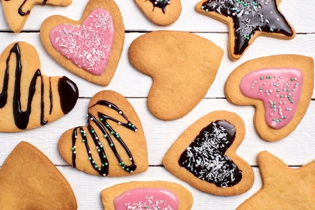 Hausgemachte shortbread-kekse, lockige kekse mit rosa zuckerguss und schokolade.