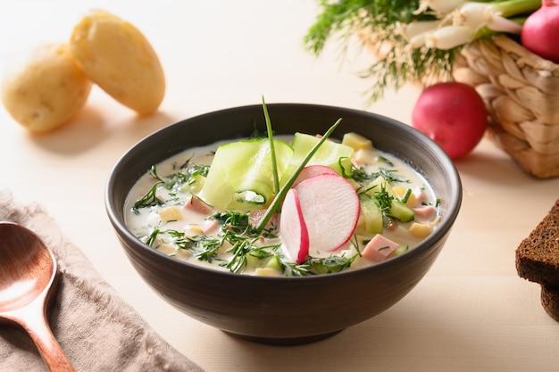 Hausgemachte sommer okroshka suppe mit kefir und sommergemüse auf hellem holztisch. nahaufnahme.