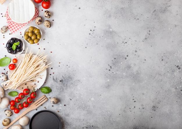 Hausgemachte spaghetti-nudeln mit wachteleiern mit einer flasche tomatensauce und käse. klassisches italienisches dorfessen. knoblauch, champignons, schwarze und grüne oliven, pfanne und spatel