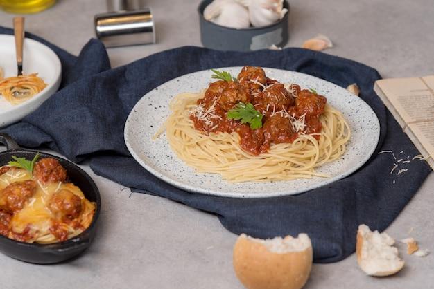 Hausgemachte spaghetti oder nudeln mit fleischbällchen und käse in tomatensauce in eine weiße schüssel gelegt. auf dunkelblauer tischdecke auf dem tisch mit bread pie.