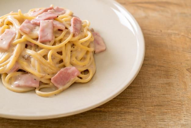 Hausgemachte spaghetti weiße sahnesauce mit schinken nach italienischer art