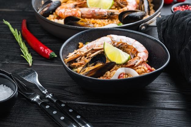 Hausgemachte spanische meeresfrüchte-paella in der bratpfanne und in der schwarzen schüssel auf schwarzem hölzernem hintergrund