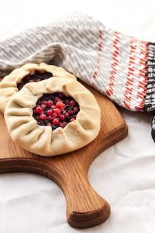 Hausgemachte süße galette mit holunderbeeren und preiselbeeren auf einem holzbrett