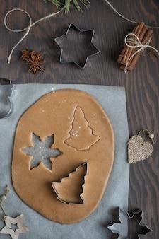 Hausgemachte süße lebkuchenplätzchen geschnitten von pikantem gewürztem gebäckteig auf holztisch mit schneidern