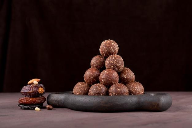 Hausgemachte süßigkeiten auf holzbrett energy balls sind ein gesunder dörrobst-snack