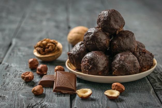 Hausgemachte süßigkeiten aus nüssen, getrockneten früchten, schokolade und honig auf einem teller auf einem schwarzen tisch.