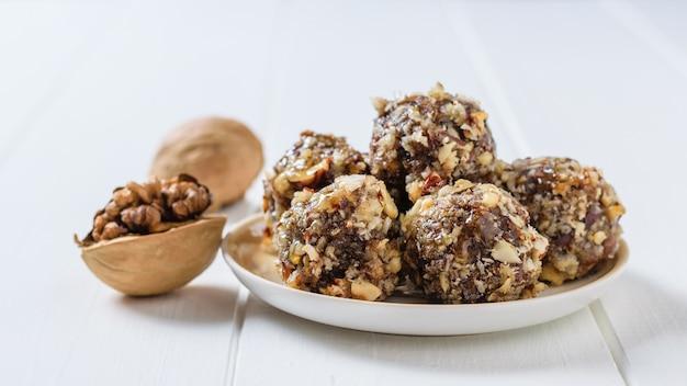 Hausgemachte süßigkeiten aus nüssen, getrockneten früchten, schokolade und honig auf einem teller auf einem weißen rustikalen tisch.