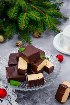 Hausgemachte süßigkeiten vogelmilch mit schokoladenglasur und karamellauflauf auf einem grauen tisch.