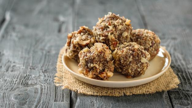 Hausgemachte süßigkeiten von hand aus nüssen, getrockneten früchten und honig auf einem teller auf einem schwarzen tisch.
