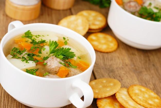 Hausgemachte suppe mit fleischbällchen auf eichentisch