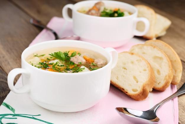 Hausgemachte suppe mit fleischbällchen auf holztisch