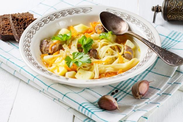 Hausgemachte suppe mit nudeln, kartoffeln, karotten, sellerie, geflügel, auf einer baumwollserviette. scheiben roggenbrot, knoblauch und pfeffer fügen einen rahmen hinzu.