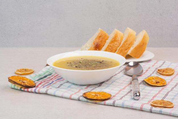 Hausgemachte suppe und brotscheiben auf tischdecke.