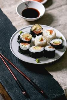 Hausgemachte sushi-rollen mit lachs, japanischem omelett, avocado, wasabi und sojasauce mit holzstäbchen auf grauem papier über schwarzer holzoberfläche. abendessen im japanischen stil