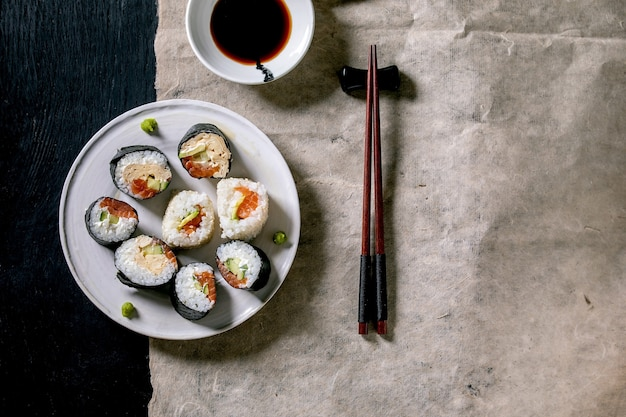 Hausgemachte sushi-rollen mit lachs, japanischem omelett, avocado, wasabi und sojasauce mit stäbchen auf grauem papier über schwarzer holzoberfläche, draufsicht, flache lage. abendessen im japanischen stil