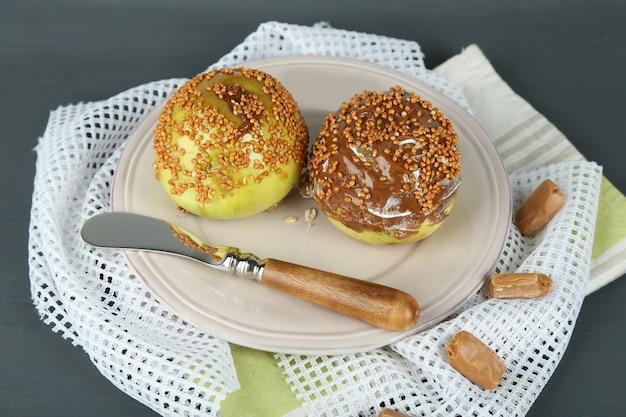Hausgemachte taffy-äpfel, auf serviette, auf holzuntergrund