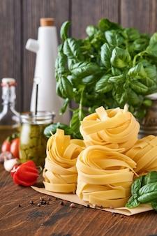 Hausgemachte tagliatelle-nudeln in braunem papier auf weißem hintergrund mit olivenöl, pesto, basilikum und knoblauch