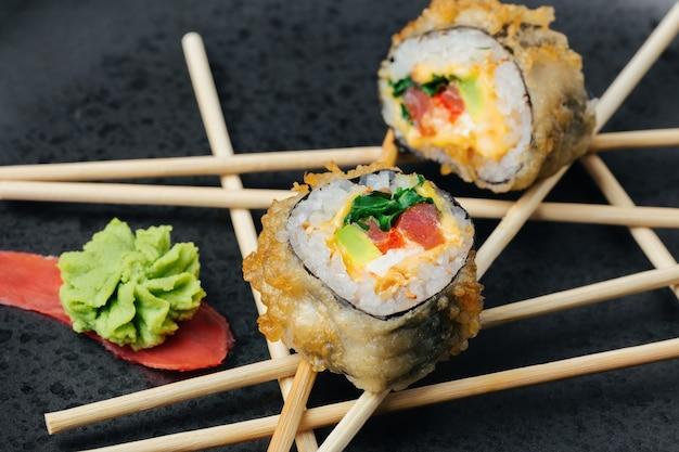 Hausgemachte thunfisch-sushi-rolle mit avocado und käse in einer knusprigen panade auf einer dunklen steinplatte.