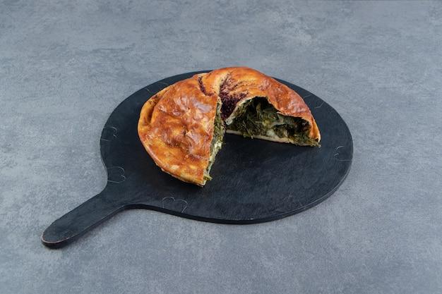 Hausgemachte torte gefüllt mit grüns auf schwarzem schneidebrett.