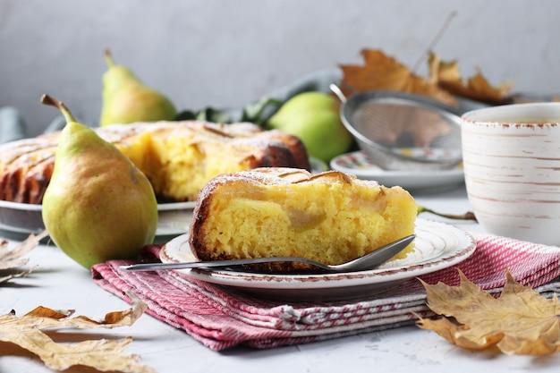 Hausgemachte torte mit birnen, tasse kaffee und herbstlaub auf hellgrauem hintergrund. stillleben
