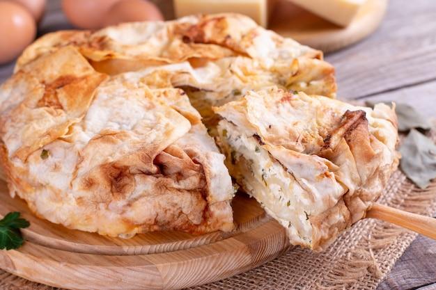 Hausgemachte torte mit käse und kräutern auf dem tisch
