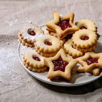 Hausgemachte traditionelle linzer shortbread kekse mit roter marmelade und puderzucker auf keramikplatte über leinentischdecke. quadratisches bild