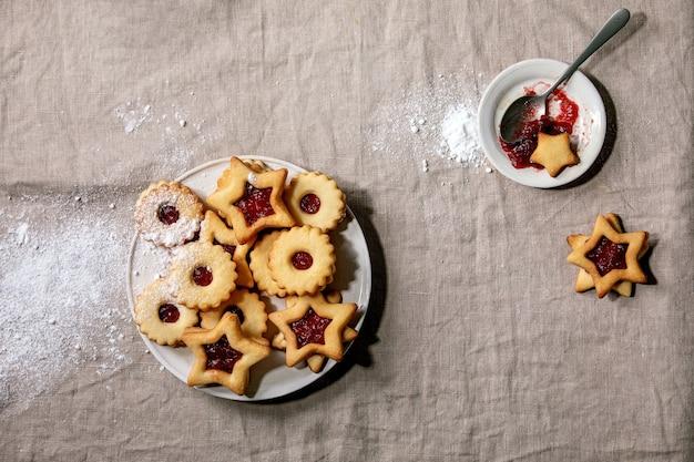 Hausgemachte traditionelle linzer shortbread-kekse mit roter marmelade und puderzucker auf keramikplatte über leinentischdecke