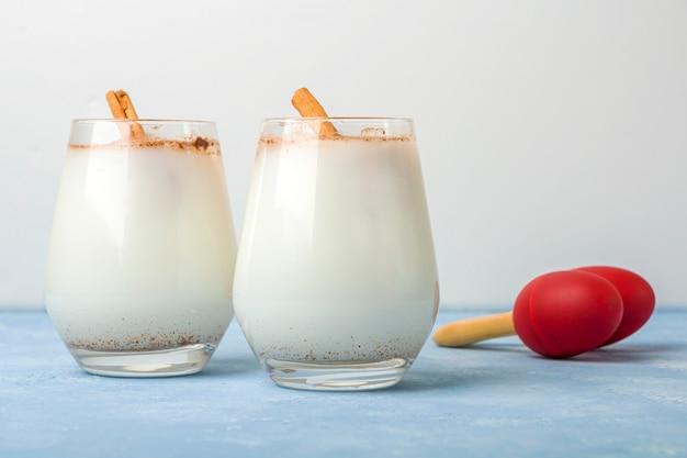 Hausgemachte traditionelle mexikanische reis horchata in einem glas und maracas auf blau. frisches kühles getränk oder cocktail aus reis, vanille und zimt oder mandel. cinco de mayo hintergrund