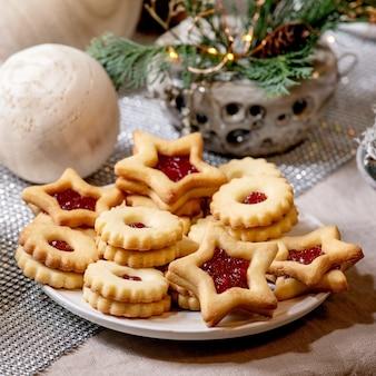 Hausgemachte traditionelle weihnachts-linz-keksplätzchen mit roter marmelade auf dem teller. trend holz umweltfreundliche weihnachtsdekorationen auf leinentischdecke. feiertagstabelleneinstellung. quadratisches bild