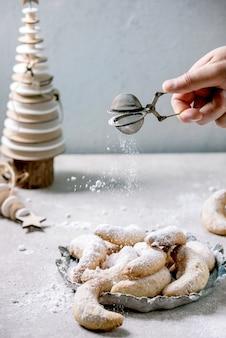 Hausgemachte traditionelle weihnachts-mürbeteig-vanille-halbmonde mit puderzucker, der vom sieb besprüht wird. auf keramikplatte mit hölzernen weihnachtsdekorationen über hellgrauer oberfläche.