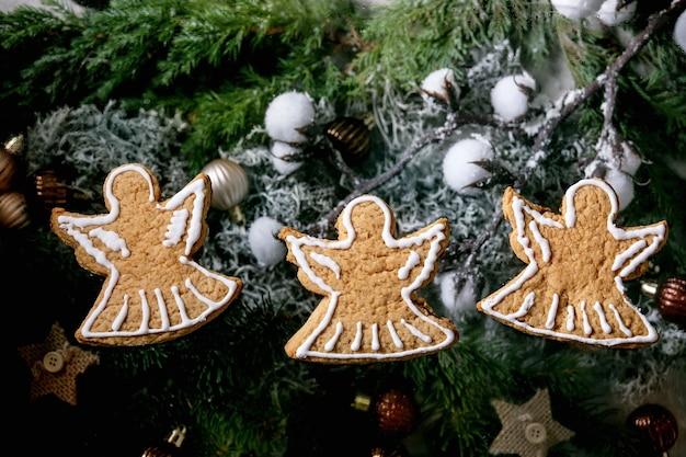Hausgemachte traditionelle weihnachtslebkuchenplätzchen mit zuckerguss verziert. drei lebkuchenengel mit weihnachtsschmuck und tannenbaum