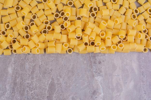 Hausgemachte ungekochte nudeln isoliert auf der marmoroberfläche