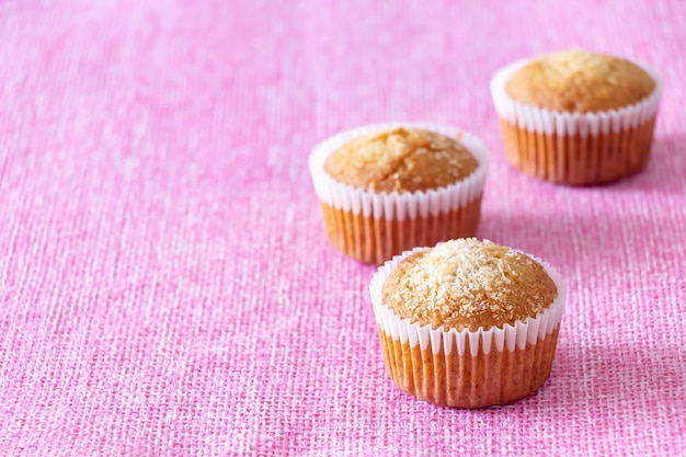 Hausgemachte vanille-muffins mit kokospulver rosa hintergrund textfreiraum selektive fcus