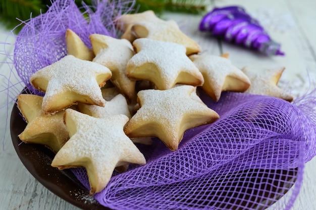 Hausgemachte vanillekekse in sternförmiger dekoration mit puderzucker auf einer lila serviette. nahansicht