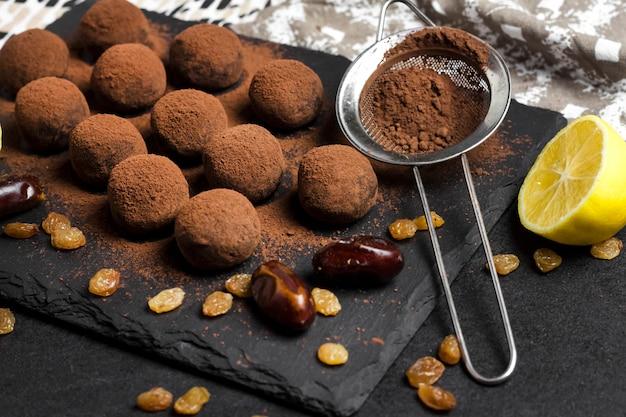 Hausgemachte vegane trüffel mit getrockneten früchten, walnüssen und rohem kakaopulver auf schwarzem schieferteller.