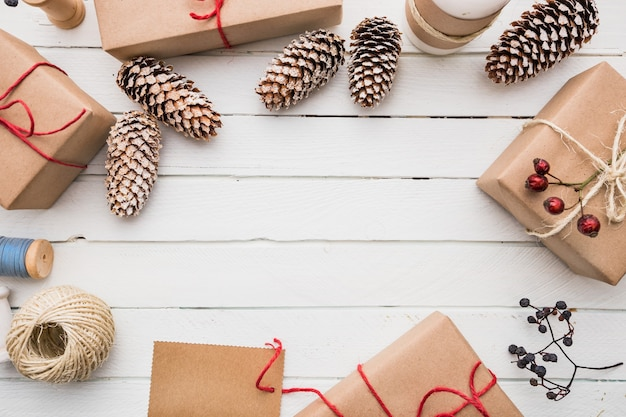 Hausgemachte verpackte rustikale braune papierpakete mit verschiedenen natürlichen dingen auf weißer holzoberfläche