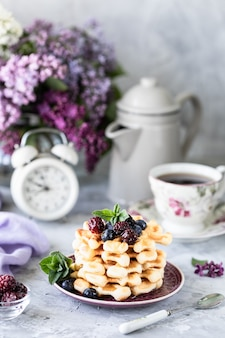 Hausgemachte waffeln mit beeren und honig, eine tasse kaffee auf dem tisch mit einem strauß flieder