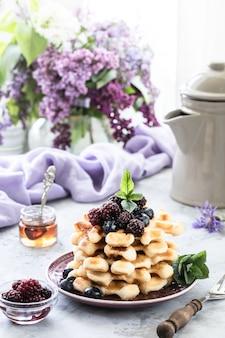 Hausgemachte waffeln mit beeren und honig, eine tasse kaffee auf dem tisch mit einem strauß flieder.
