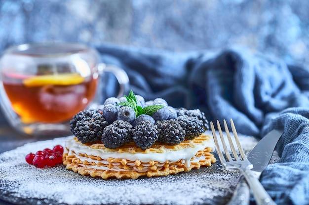 Hausgemachte waffeln mit blaubeeren und brombeeren, puderzucker auf einer steinplatte mit früchten. geringe schärfentiefe.