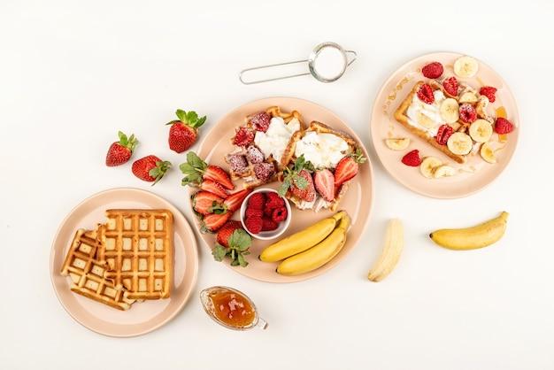 Hausgemachte waffeln mit früchten und beeren, sahne und honig in einem teller auf weißem tisch. flache lage, draufsicht, kopierraum.