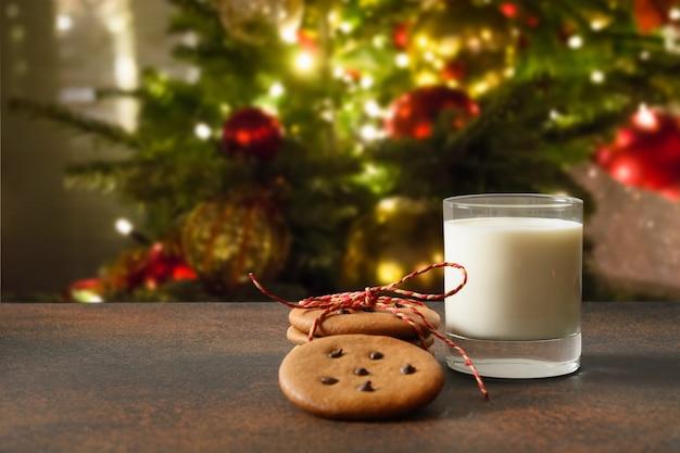 Hausgemachte weihnachtsplätzchen und ein glas milch für santa nahe weihnachtsbaum