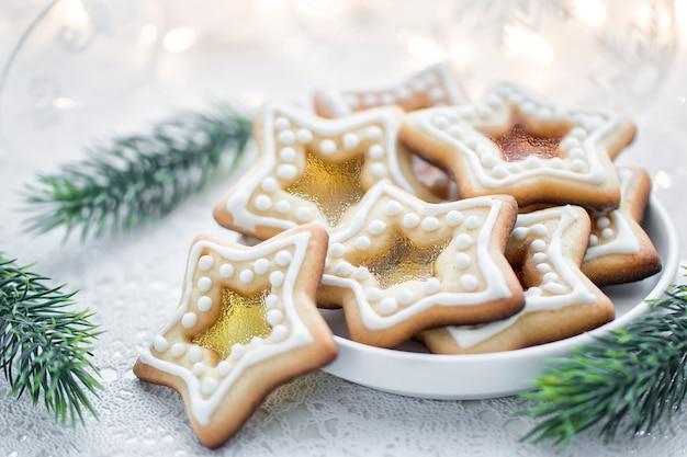 Hausgemachte weihnachtssternform zuckerkaramellplätzchen auf weißem hintergrund mit tannenzweigen