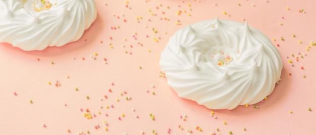 Hausgemachte weiße luft meringen und süßwaren dekorationen auf rosa, banner