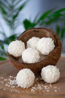 Hausgemachte weiße pralinen in kokosflocken in nussschale auf holzbrett und grünem palmblatt.