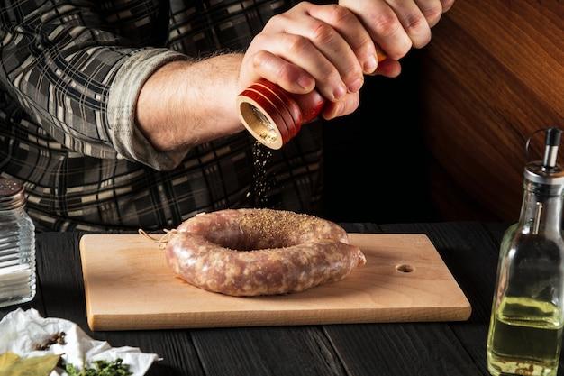 Hausgemachte wurst mit den händen des küchenchefs kochen