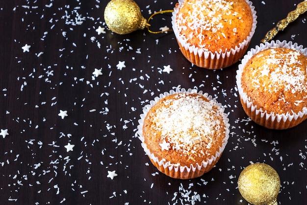 Hausgemachte zitronenmuffins schmücken den dunklen hintergrund des kokosnusspulvers. neujahrs- und weihnachtskonzept. selektiver fokus.
