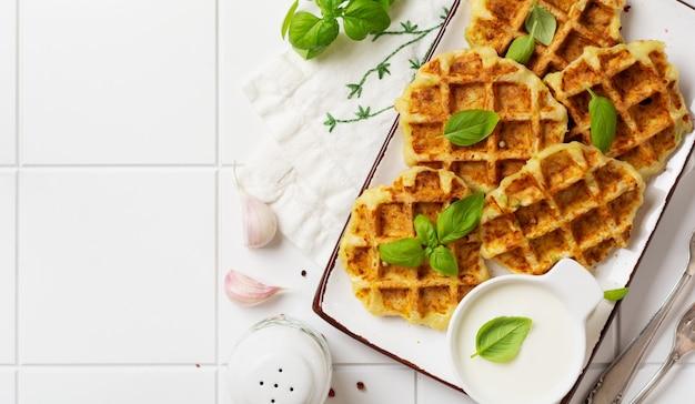 Hausgemachte zucchini-waffeln mit käse, sause und blattbasilikum auf weißem tisch. konzept der ketodiätnahrung. selektiver fokus.