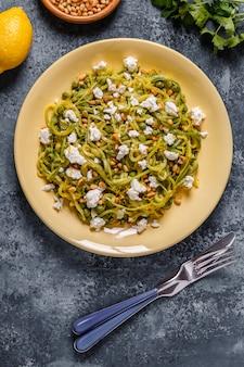 Hausgemachte zucchini zoodles pasta mit pinienkernen und feta.