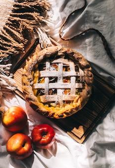 Hausgemachter apfelkuchen auf einem holzbrett mit zimt und einer goldenen kruste. herbstsaison